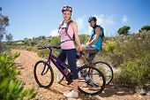 Fit couple cycling up mountain trail smiling on a sunny day
