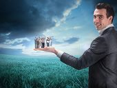 Composite image of businessman holding business team against blue sky over green field