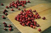 a pile of pink peppercorns on a rustic wooden table
