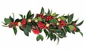 Christmas floral decoration of holly, baubles and pine cones over white background.