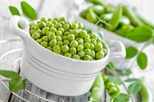 pic of green pea  - Raw green peas and in a pods on a table - JPG