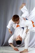 In white judogi two athletes are training throws