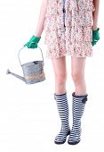 Young woman in rubber boots holding watering can, isolated on white