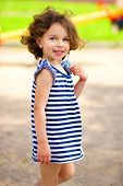 Cute little girl is playing in playground, outdoor shoot
