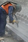 foto of sandblasting  - A tradesman sandblasts steel beams for a building project - JPG