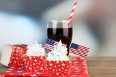 American patriotic holiday cupcakes and glass of cola on wooden table