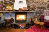 picture of stone house  - A fireplace in a rural home with shoes and boots drying close to the heat - JPG