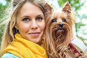 Close up portrait smiling young blonde with yorkshire terrier outdoor.