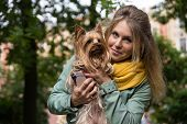 Young smiling pretty blonde woman in city park. Small yorkshire terrier is on her hands.