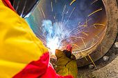 stock photo of pipe-welding  - Welder welding a pipe on a terrain
