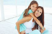 stock photo of 7-year-old  - Mother with her 7 years old daughter having fun at beach in summer - JPG