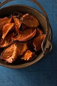 Aromatic, dried orange potpourri leaves  in copper bowl
