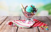 Chocolate ice cream with multicolor candies and wafer rolls in glass bowl, on color wooden table, on