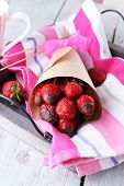 Strawberry in chocolate on skewers in paper bag on table close-up
