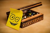 Drawn smiley face on a post-it note sticked on a jewelry box