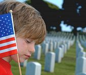 stock photo of inhumane  - Child with American flag in cemetery - JPG