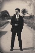 Vintage Photo Of A Gentleman Standing On The Road. Black And White