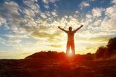 stock photo of joy  - Silhouette of a man with hands raised in the sunset concept for religion - JPG