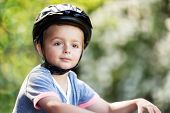 Boy wearing a cycling helmet riding a bicycle concept for safety, childhood and freedom