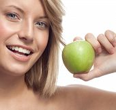 portrait of attractive  caucasian smiling woman blond isolated on white studio shot eating green app