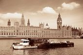 Big Ben and House of Parliament in London with boat in Thames River.