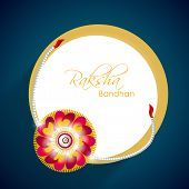 Beautiful rakhi with golden circle frame on blue background for Happy Raksha Bandhan celebrations.