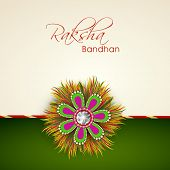 Beautiful rakhi on beige and green background for Happy Rakhsha Bandhan celebrations.