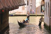 Gondolier Sails With Tourists Sitting In A Gondola Down The Narrow Channel In Venice, Italy