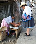 HUARAZ, PERU - AUGUST 21: Peruvian peasant woman selling fried pork meat on the streets of Huaraz, P