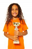 pic of prize winner  - Close portrait of happy African black girl with curly hair holding soccer winners cup prize and winners prize cup wearing sport team uniform standing isolated on white and smiling - JPG