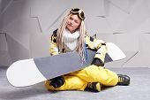 Young woman sitting on floor with snowboard
