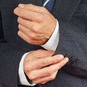 Man fastened the buttons on sleeve business suit closeup