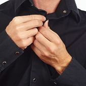 Hands a guy unbutton his black shirt closeup