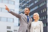 business, partnership, gesture success and people concept - smiling businessman and businesswoman pointing finger over office building