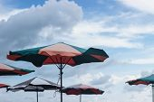 colorful parasols umbrellas with cloudy blue sky behind