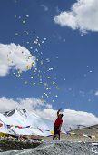 Man Scattering Buddhist Prayer Sheets At Tangangla Pass On The Way To Leh Kalachakra Festival