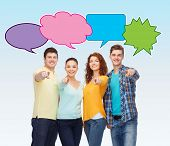 friendship, communication, gesture and people concept - group of smiling teenagers over blue background with text bubbles