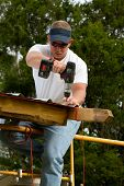picture of rafters  - Construction worker uses a battery powered drill to attach corrugated sheet metal to the rafters of a building - JPG