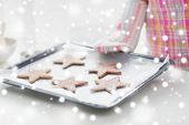 christmas, food, holidays and people concept - close up of woman in apron and oven glove with cookies on oven tray