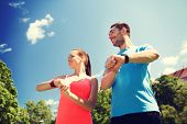 fitness, sport, training, technology and lifestyle concept - two smiling people with heart rate watches outdoors