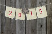 Year 2015 on antique parchment paper hanging on clothesline with heart by wooden background