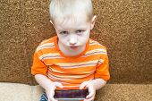 little boy sitting on the couch playing in the smartphone