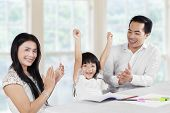 stock photo of applause  - Cheerful girl finishing her homework and getting applause from her parents - JPG