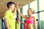 sport, fitness, lifestyle and people concept - smiling man and woman making high five in gym