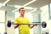 sport, fitness, lifestyle and people concept - man doing exercise with barbell in gym