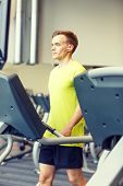 sport, fitness, lifestyle, technology and people concept - man with earphones exercising on treadmill in gym