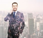 business, people, development and technology concept - smiling young businessman over transparent city background