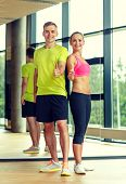 sport, fitness, lifestyle and people concept - smiling man and woman showing thumbs up in gym