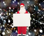 christmas, holidays, advertisement and people concept - man in costume of santa claus with white blank billboard over snowy night city background