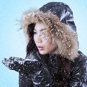 Young Lady Blowing Snow On Palms